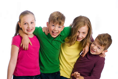 children at play: Group of four young kids in colorful shirts having fun Stock Photo