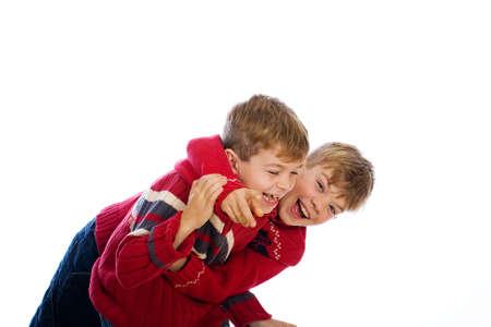 hermanos jugando: dos chicos guapos jóvenes que usan suéteres rojos Foto de archivo