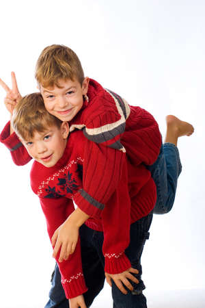 two cute young boys wearing red sweaters
