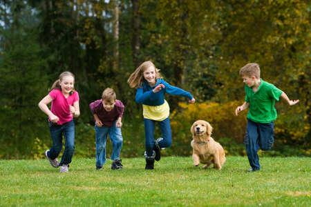 Groep kinderen en een hond tegen elkaar racen Stockfoto