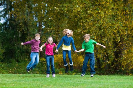 boy and girl holding hands: group of children holding hands jumping in the air