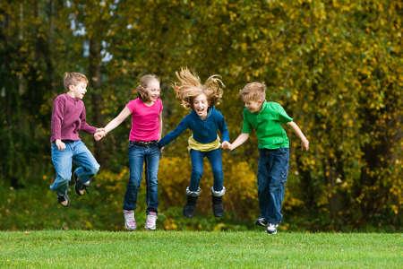 grupo de niños de la mano saltando en el aire