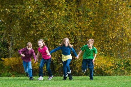 草の上を実行している子供たちのグループ 写真素材