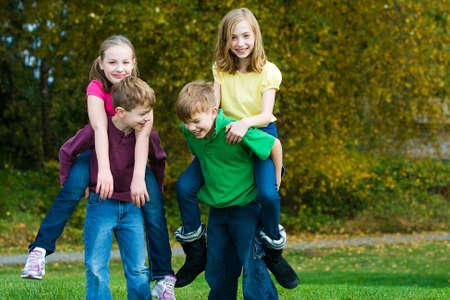 piggyback ride: Group of kids playing at a park outside Stock Photo