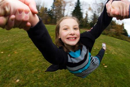 Kind swingende in een cirkel door haar armen