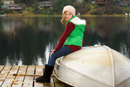 stocking cap: cute young girl with a pretty smile on a boat dock at a lake