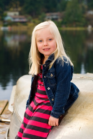 cute young girl with blond hair playing at a lake on a boat dock Stock Photo - 12029152