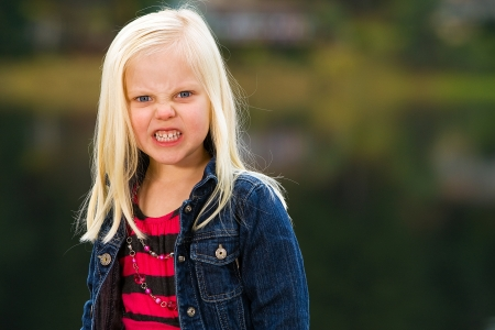 angry blonde: Angry, scary young child with freaky expression Stock Photo