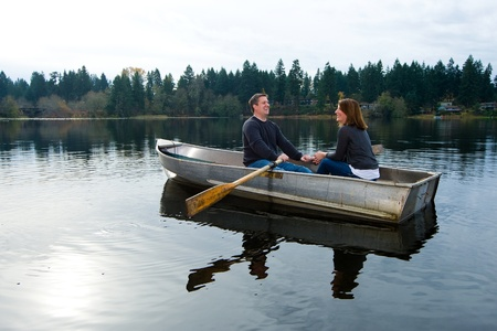 Happy couple in a small row boat on a quiet lake