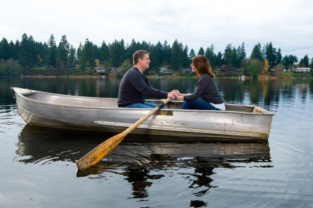 row: Happy couple in a small row boat on a quiet lake