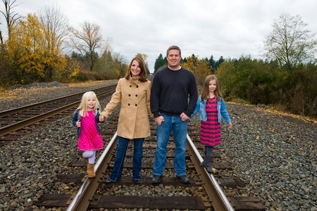 Happy family holding hands walking on train tracks photo
