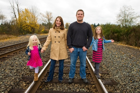 Happy family holding hands walking on train tracks