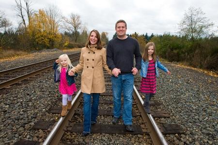 family walking: Happy family holding hands walking on train tracks