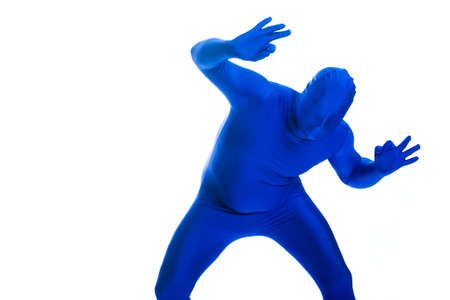 featureless: Faceless, anonymous man in a blue body suit giving an OK sign. Stock Photo