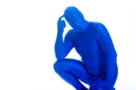 scratching head: Faceless man in a blue body suit scratching his head.
