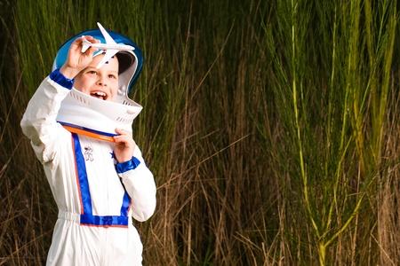 Jonge jongen in een astronaut pak het spelen met een speelgoed vliegtuig.