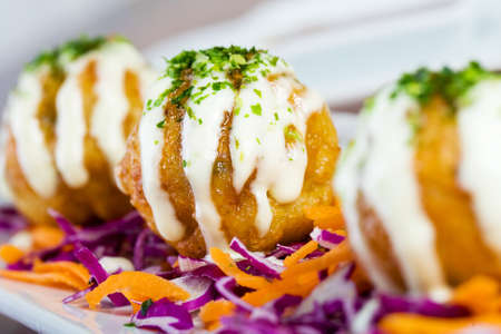 Deep fried fish balls at an Asian restaurant smothered with melted cheese