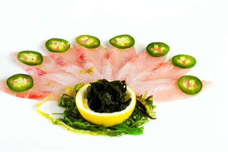 Raw fish with spicy jalapeno pepper fanned like peacock feathers. photo