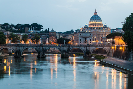 Angel bridge and St. Peters Basilica copula in Rome, Italy during sunset