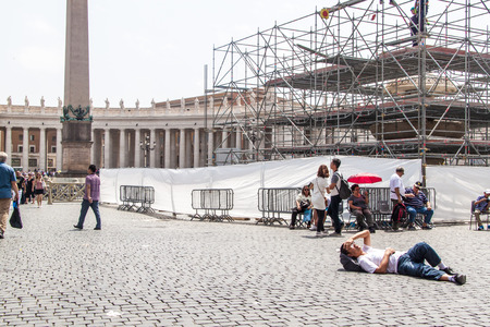 ROME, ITALY - JUNE 25: Tourists visit St. Peters Square in Vatican on June 25, 2014. Saint Peters Square is among most popular pilgrimage sites for Roman Catholics.