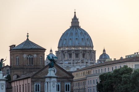 in copula: St. Peters Basilica copula and other buildings in Rome, Italy during sunset