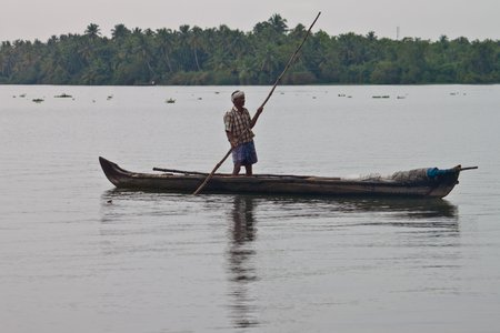 backwaters: BACKWATERS, INDIA - AUGUST 24: Man in a canoe on August 24, 2011 in Backwaters, India. The Kerala Backwaters are a network of interconnected canals, rivers, lakes and inlets.