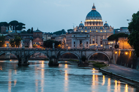 Angel bridge and St. Peters Basilica copula in Rome, Italy during sunset photo