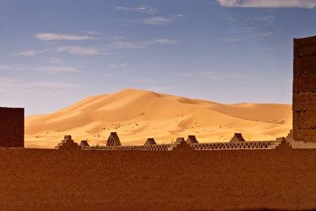 erg chebbi: Wall of kasbah and sand dune at Erg Chebbi, Morocco Stock Photo