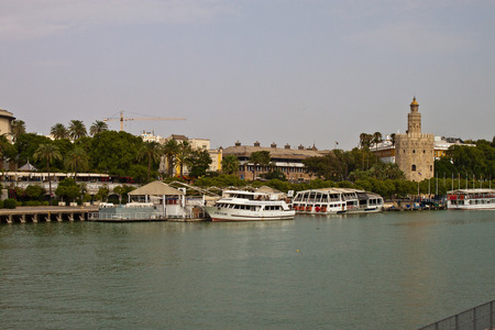 golde: SEVILLE, SPAIN - AUGUST 9: Sightseeing boats at the Guadalquivir river and Torre del Oro (Gold Tower) in Seville on June 9, 2010 in Seville, Spain. Editorial