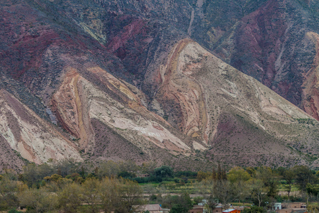 stratification: Village Maimara under colorful rock called Paleta del Pintor (Painters Palette) in Quebrada de Humahuaca valley, Argentina