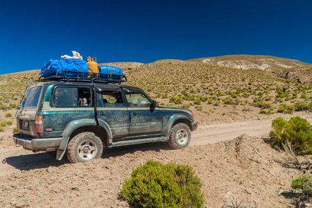 lipez: SOUTHWESTERN BOLIVIA - APRIL 14, 2015: 4WD vehicle carries group of tourists at the popular Salar de Uyuni tour. Editorial