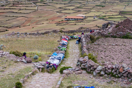locals: AMANTANI, PERU - MAY 15, 2015: Locals sell hand made products at the path leading to Pachamama hill on Amantani island in Titicaca lake, Peru