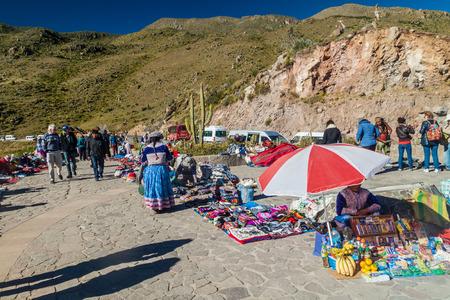 condor: CABANACONDE, PERU - MAY 27, 2015: Tourists and market vendors at the Cruz Del Condor viewpoint.