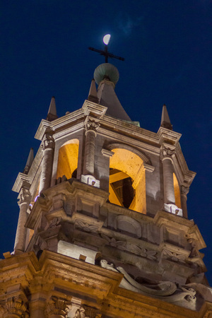 plaza de armas: Tower of a cathedral and the moon at Plaza de Armas square in Arequipa, Peru. Stock Photo