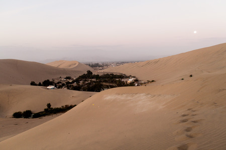 moon  desert: Desert oasis Huacachina near Ica, Peru. Moon visible.
