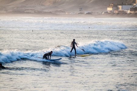 swells: HUANCHACO, PERU - JUNE 6, 2015: People surf in waves of an ocean in Huanchaco, Peru. Editorial