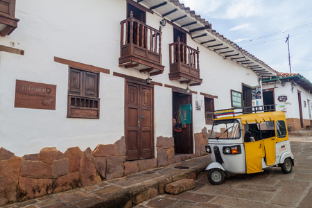 mototaxi: BARICHARA, COLOMBIA - SEPTEMBER 17, 2015: Mototaxi (tuk tuk) and old colonial houses in Barichara village, Colombia Editorial