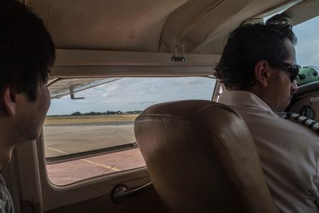 cessna: CIUDAD BOLIVAR, VENEZUELA - AUGUST 16, 2015: Pilot and a passenger of a small Cessna 210 Centurion airplane at the airport of Ciudad Bolivar, Venezuela
