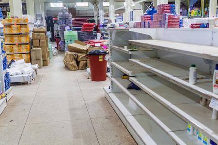 looting: SANTA ELENA DE UAIREN, VENEZUELA - AUGUST 12, 2015: Empty shelves in a supermarket. Shortages of basic supplies are common in Venezuela.