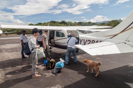 cessna: CANAIMA, VENEZUELA - AUGUST 16, 2015: Passengers of Cessna 210 Centurion airplane at the airport in Canaima village, Venezuela Editorial