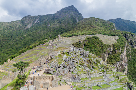 machu picchu: MACHU PICCHU, PERU - MAY 18, 2015: Crowds of visitors in House of the High Priest at Machu Picchu ruins, Peru. Stock Photo