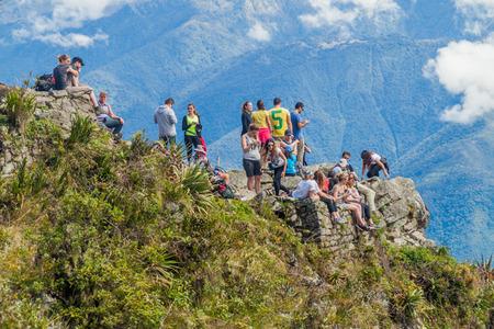 MACHU PICCHU, PERU - MAY 18, 2015: Tourists at the peak of Machu Picchu mountain, Peru