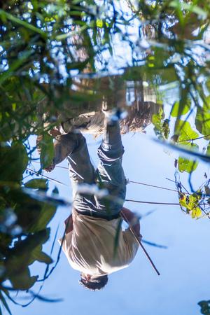 guia de turismo: MADIDI, BOLIVIA - 8 de mayo, 2105: Reflexión del agua de un nativo de caza guía turístico en una selva del Parque Nacional Madidi, Bolivia Editorial