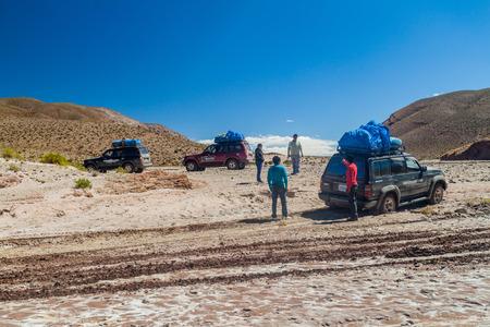 avaroa: SOUTHWESTERN BOLIVIA - APRIL 14, 2015: 4WD vehicles carry group of tourists at the popular Salar de Uyuni tour.