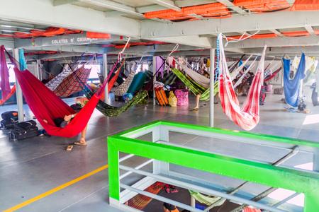 plies: AMAZON, BRAZIL - JUNE 23, 2015: Passengers of hammock deck at the boat Diamante which plies river Amazon between Tabatinga and Manaus, Brazil.