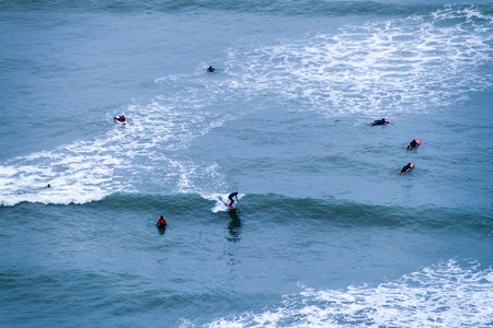 LIMA, PERU - JUNE 4, 2015: People surf on waves of an ocean. Miraflores district of Lima, Peru.