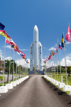 french model: KOUROU, FRENCH GUIANA - AUGUST 4, 2015: Model of Ariane 5  space rocket and flags of ESA members at Centre Spatial Guyanais (Guiana Space Centre) in Kourou, French Guiana