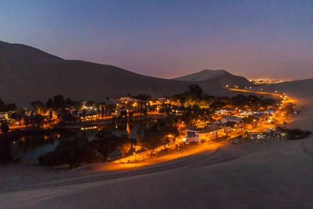 Evening view of illuminated desert oasis Huacachina near Ica, Peru