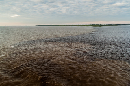 confluence: The Meeting of Waters (Encontro das Aguas) is the confluence between the Rio Negro river, with dark water, and lighter Amazon river or Rio Solimoes Stock Photo