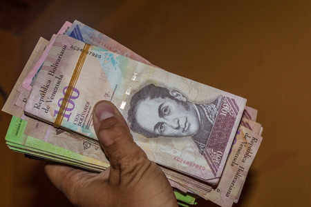 venezuelan: Stack of Venezuelan currency (Bolivar Fuerte) is hold in the hand. Due to hyperinflation, it is necessary to use thick stack of bills to cover basic needs.